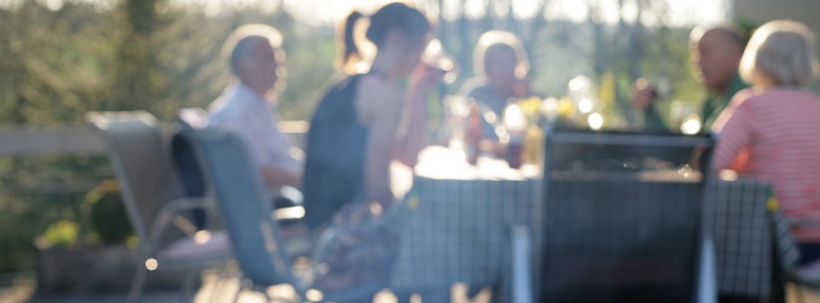 Verschiedene Generationen sitzen gemeinsam im Garten am Tisch